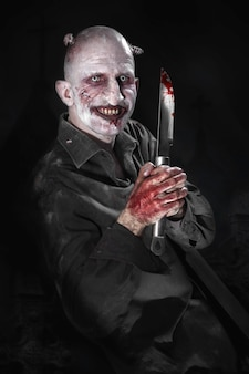 Portrait of a man with a bloody knife disguised as a zombie on a black background.