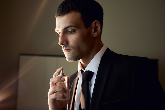 Portrait of a man with cologne in his hands