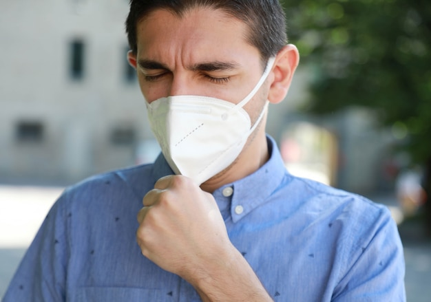 Portrait of man with face mask against sars-cov-2 coughing outdoor.
