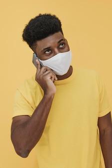Ritratto di uomo con maschera facciale e smartphone
