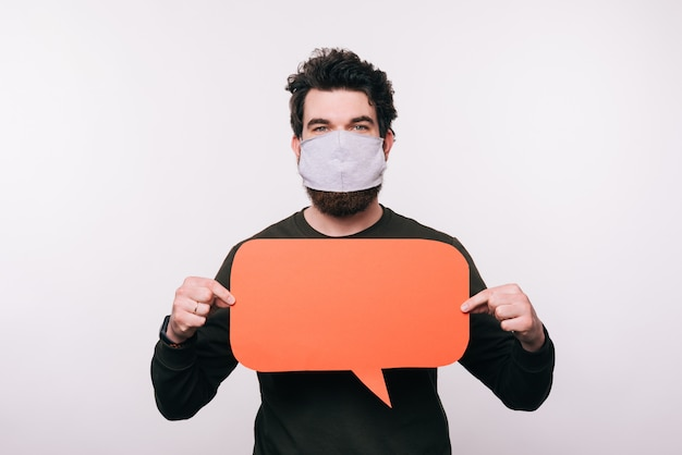 Portrait of man with facial mask holding speech bubble