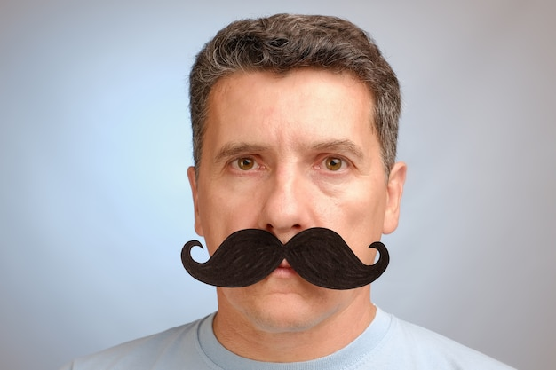 Portrait of a man with a fake mustache to attend an event in november to help men awareness health problems.