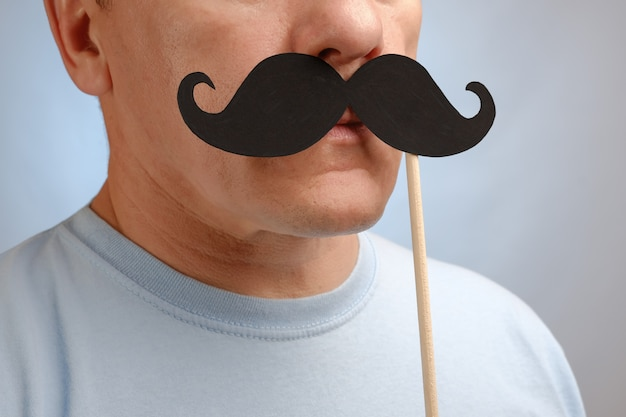 Portrait of a man with a fake mustache on stick to attend an event in november to help men awareness health problems.