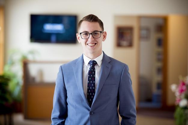 Ritratto di un uomo con gli occhiali in un abito blu con una cravatta sotto le luci con uno sfondo sfocato