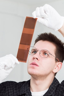 Portrait of man with glasses looking at photo strips