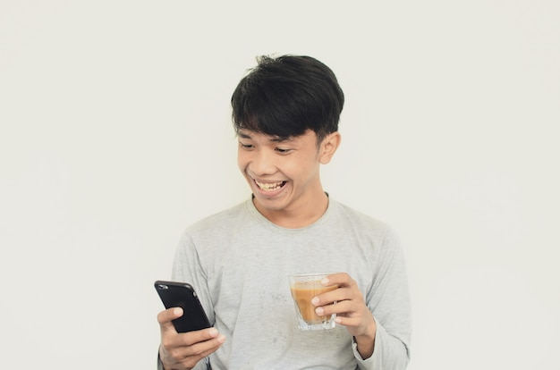Portrait of a man with a happy expression looking at his cell phone while carrying coffee