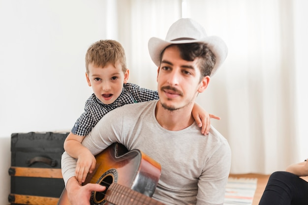 Portrait of a man with his child playing guitar