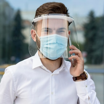 Portrait man with mask talking over phone