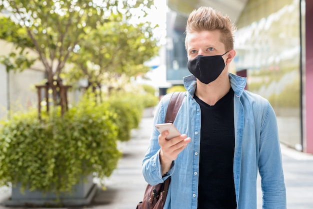 Portrait of man with mask thinking while using phone in the city outdoors