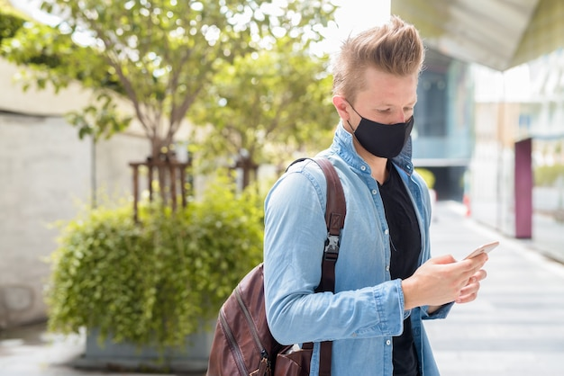Portrait of man with mask using phone in the city streets outdoors