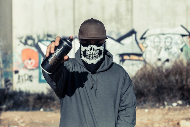 Portrait of a man with skull mask holding aerosol can