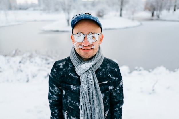 Portrait of a man with snow on his face standing outdoor with smiling face in winter snowy day at nature.