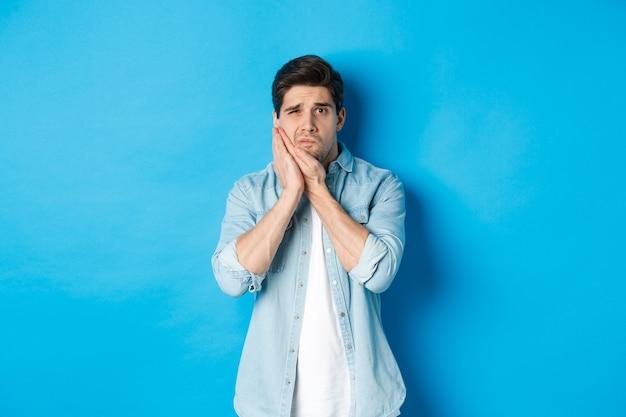 Ritratto di un uomo con mal di denti che fa smorfie di dolore e tocca la guancia, in piedi su sfondo blu