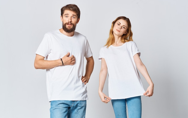 Portrait of a man and a woman in identical t-shirts teenager jeans light background. high quality photo
