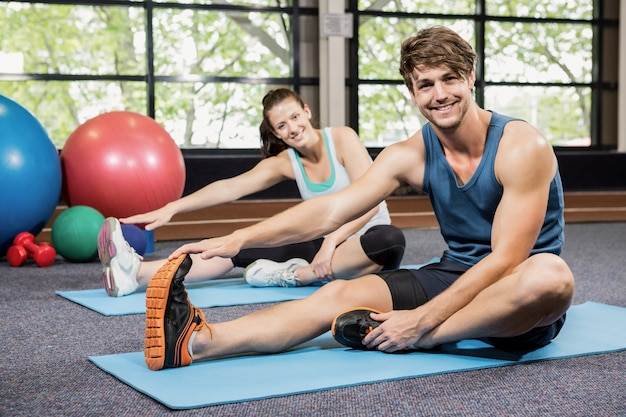 Portrait of man and woman performing fitness exercise