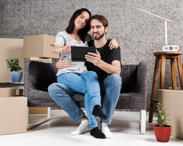 Portrait of man and woman relaxing in new apartment