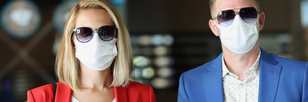 Portrait of man and woman wearing medical protective masks