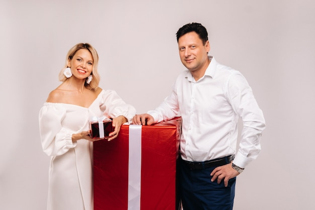 Portrait of a man and a woman with a large gift on a beige background.