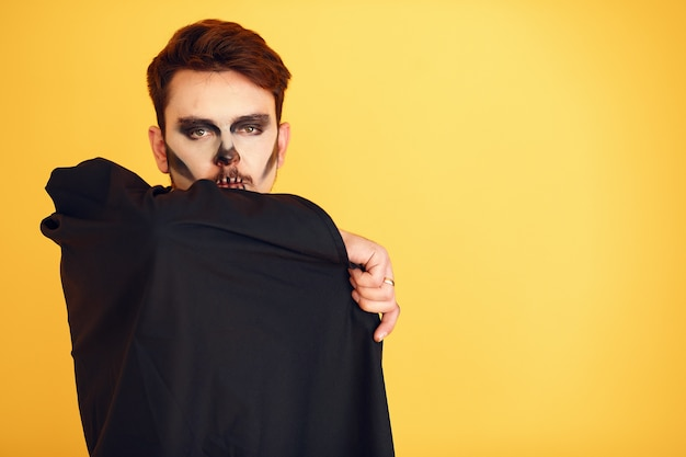 Portrait of man on yellow background. halloween skull make up showing his emotions.