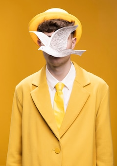 Portrait of man in yellow suit with silver pigeon in front of face