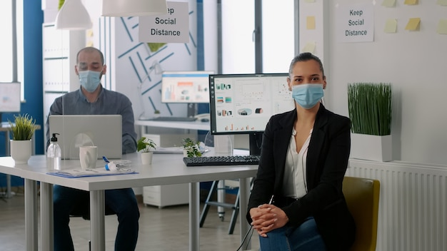 Portrait of manager woman wearing medical face mask while standing in new normal company office. colleagues working in background for marketing project respecting social distancing to avoid covid19