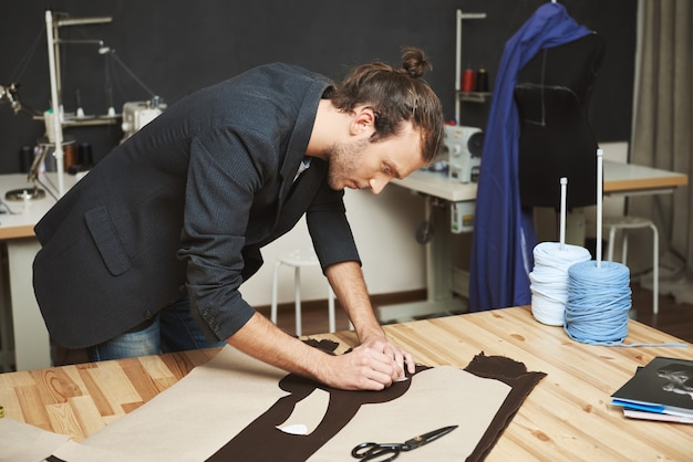 Portrait of manly good-looking adult male clothes designer with stylish hairstyle in black suit cutting out parts of future dress from fabric. man concentrated on work.