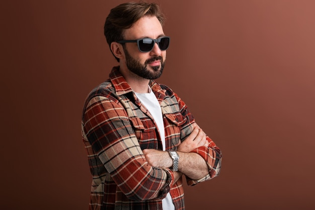 Portrait of manly handsome stylish bearded man on brown