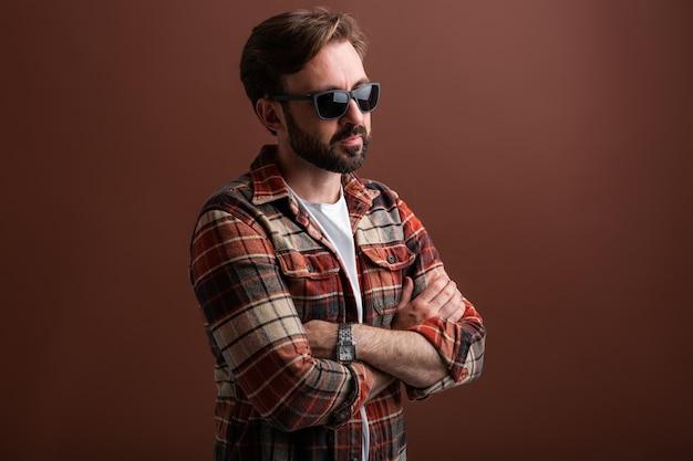 Ritratto dell'uomo barbuto alla moda bello virile su colore marrone