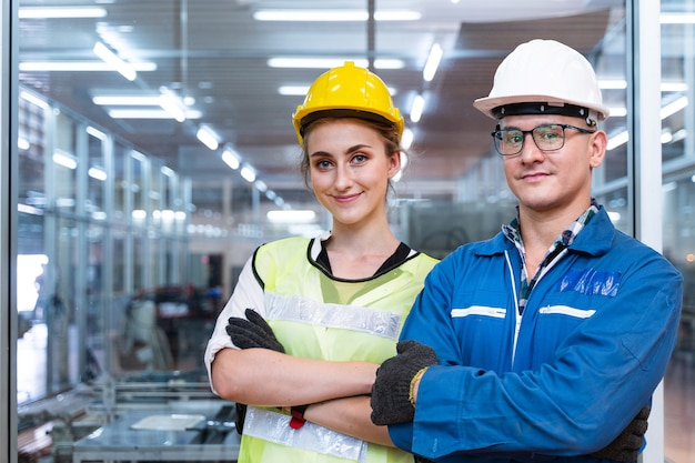 Portrait of manual man and woman worker is standing with confident with blue working suite