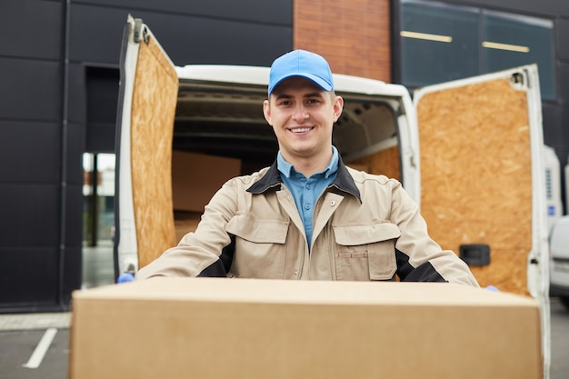 Portrait of manual worker smiling at camera while holding the big box outdoors