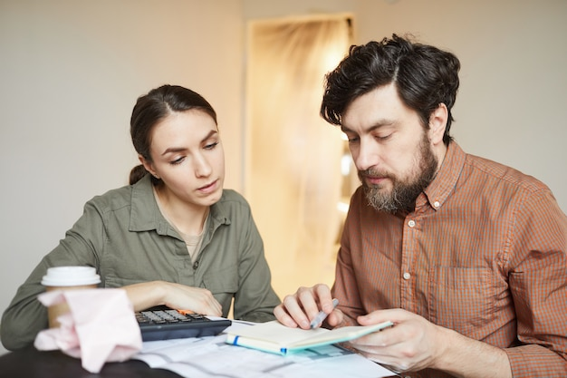 Portrait of married couple budgeting redecorations cost while sitting at table in empty room