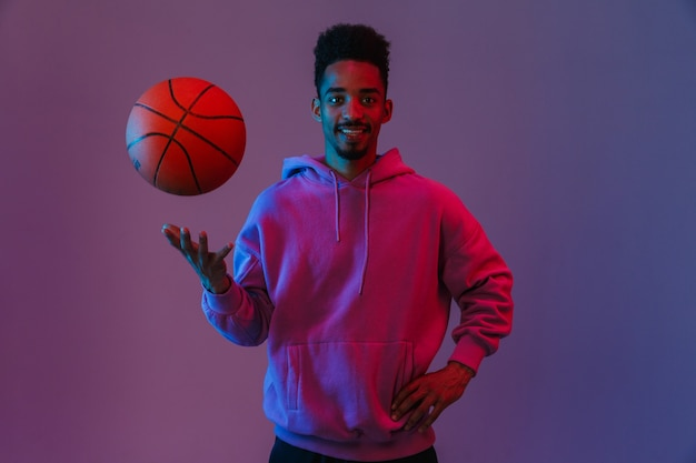 Portrait of masculine african american man in colorful hoodie posing with basketball isolated over violet wall