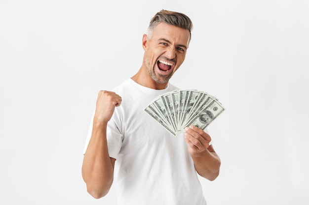 Portrait of masculine man 30s wearing casual t-shirt smiling and holding bunch of money banknotes isolated on white