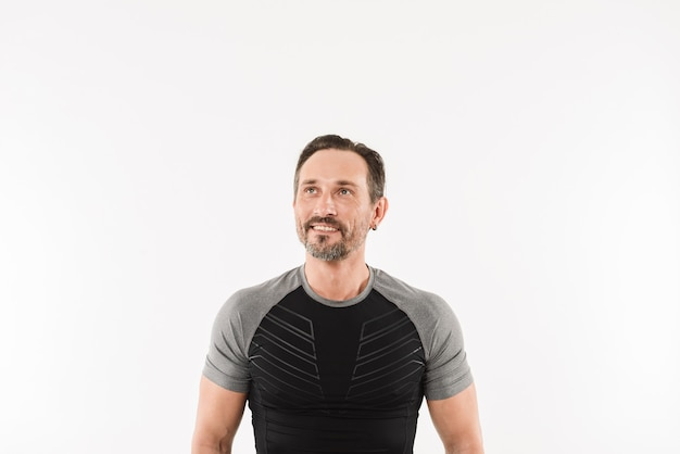 Portrait of masculine man 30s wearing sportswear looking upward on copyspace with smile and satisfied look after doing sports