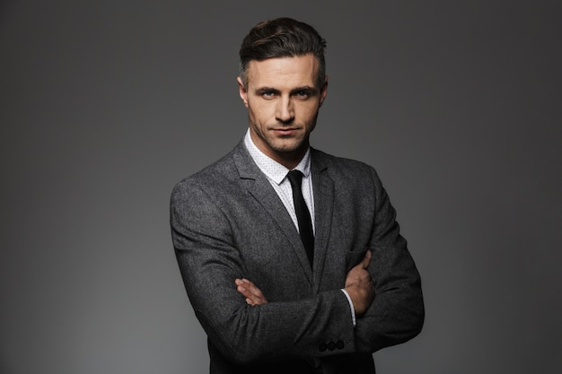 Portrait of masculine man wearing business suit posing  with serious look keeping arms folded, isolated over gray wall