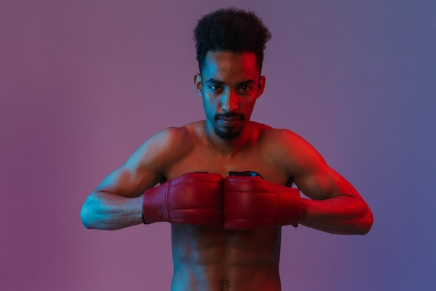 Portrait of masculine shirtless african american sportsman posingin boxing gloves isolated over violet wall