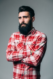 Portrait of masculinity. portrait of handsome young bearded man while standing against grey wall
