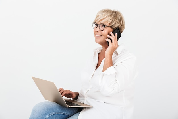 Portrait of mature adult woman wearing eyeglasses talking on smartphone while sitting with laptop computer isolated over white wall
