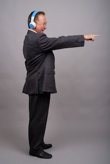 Portrait of mature asian businessman against gray wall