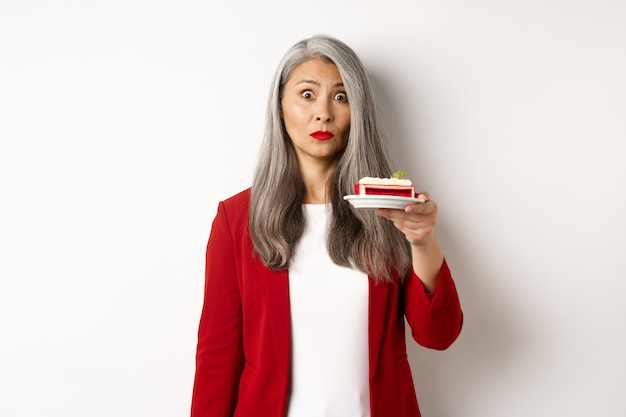 Portrait of mature asian woman on diet holding sweet cafe, looking indecisive at camera, standing over white background.