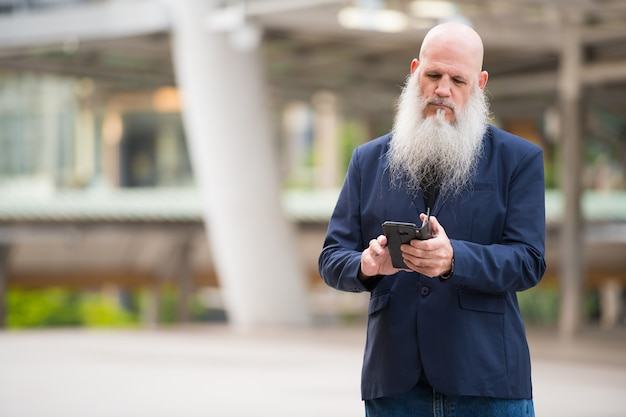 Portrait of mature bald businessman with long beard in the city streets outdoors
