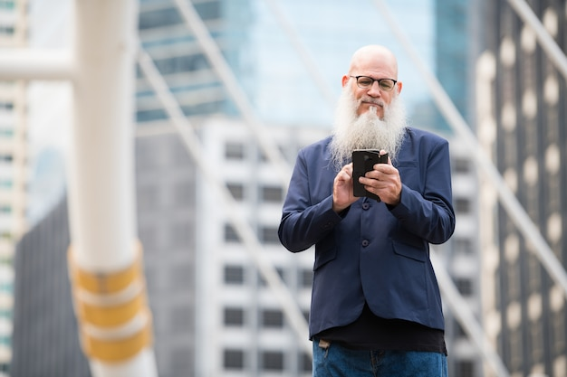 Portrait of mature bald businessman with long beard wearing eyeglasses in the city streets outdoors