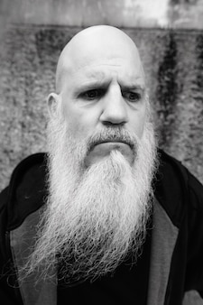 Portrait of mature bald man with long gray beard against grunge concrete wall outdoors in black and white