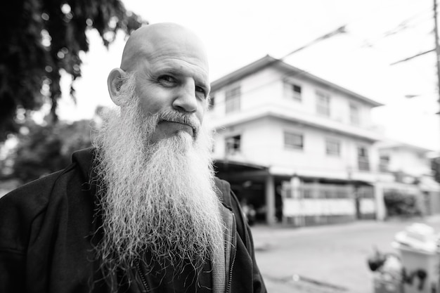 Portrait of mature bald man with long gray beard in the streets outdoors in black and white