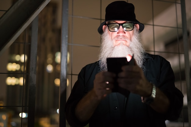 Portrait of mature bearded man looking suspicious at dark staircase