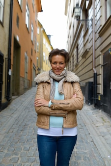 Portrait of mature beautiful scandinavian tourist woman with short hair traveling around the city of stockholm in sweden