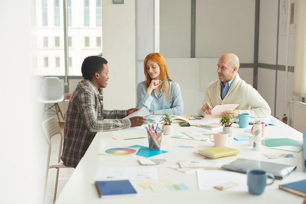 Portrait of mature business people smiling cheerfully while talking to african-american intern during interview meeting in modern white office, copy space