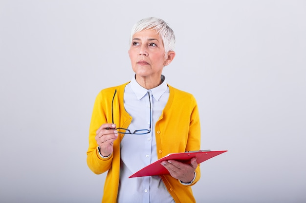 Portrait of mature business women with clipboard and document in hand with copy space isolated on white wall. thoughtful creative businesswoman looking away in office