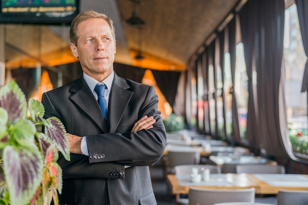 Portrait of a mature businessman with crossed arms standing in restaurant