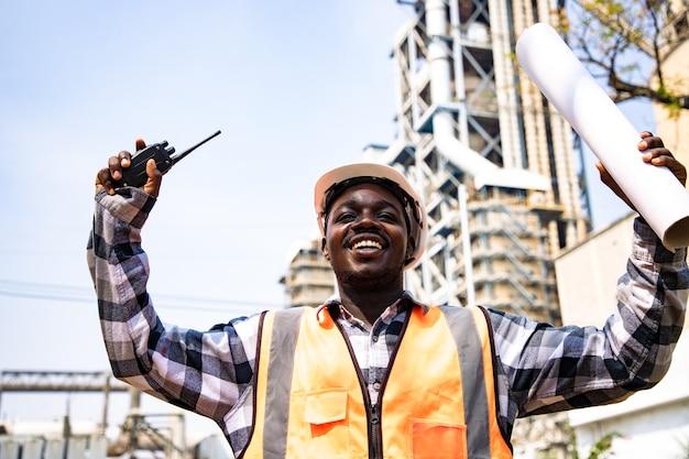 Портрет зрелого инженера-строителя, уверенно улыбающегося с яркой улыбкой на месте